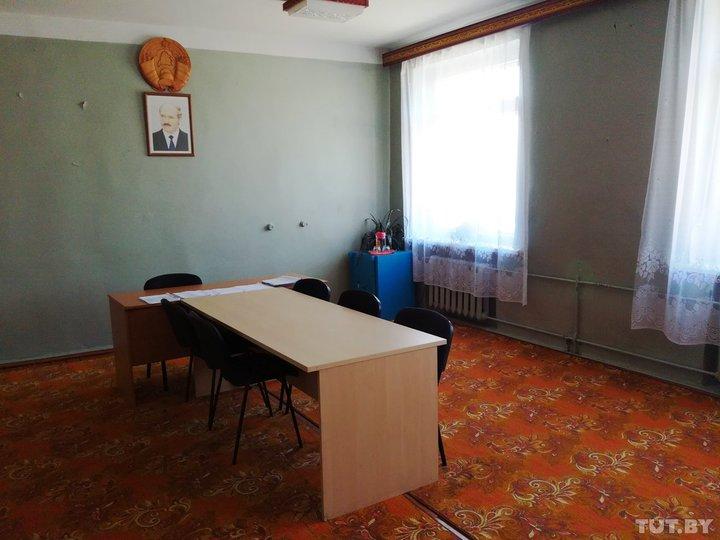 «Кабинет» главы новоиспеченного холдинга в Городищенском сельсовете. Он же — актовый зал. Из обстановки — стол, стулья, обшарпанные складные кресла у стены и массивный советский сейф в углу. Фото: TUT.by