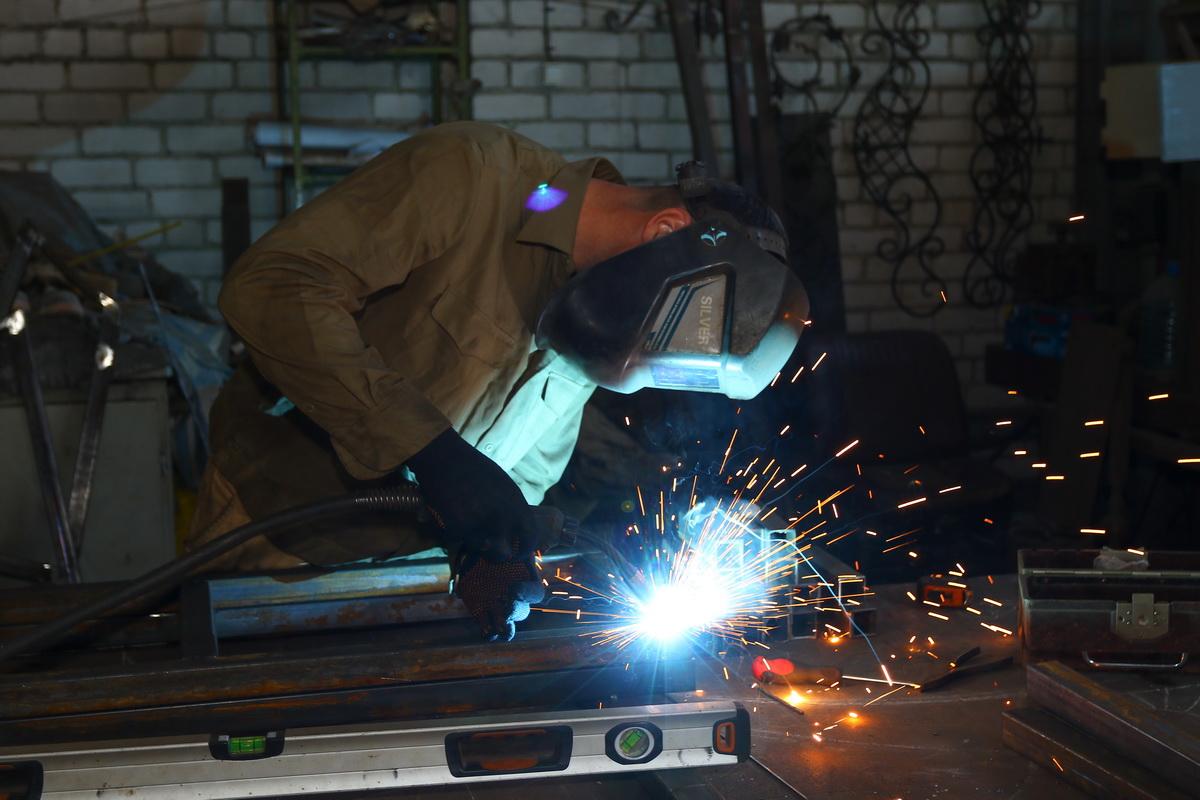 Николай Троянович сваривает детали  лестницы. Фото: Александр ЧЕРНЫЙ