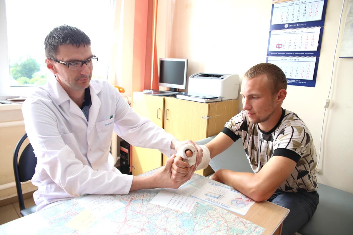Врач травматолог- ортопед Андрей Трофимович осматривает  пациента Сергея Коленду. Парень повредил сухожилие во время работы в гараже.  Фото: Евгений ТИХАНОВИЧ