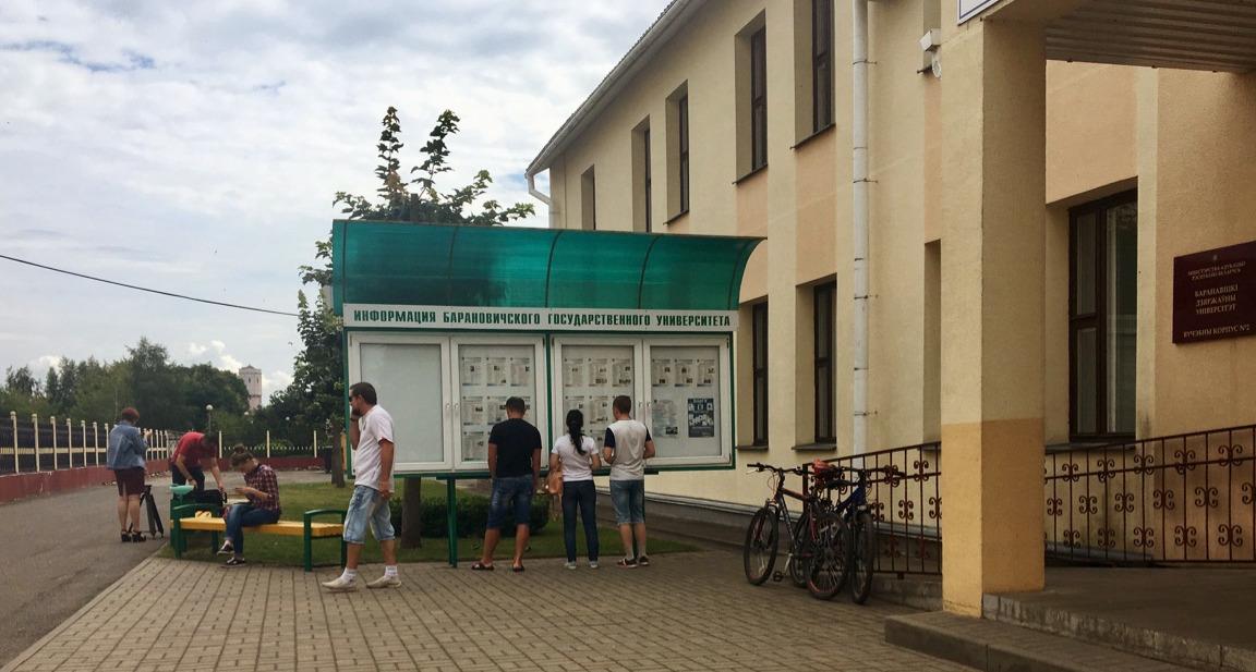 Чтобы не стоять в очереди в помещении, студенты выходят на улицу и изучают информацию на стенде.