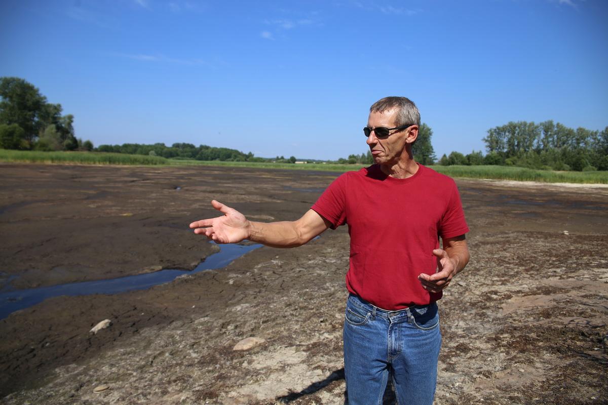 Андрей Винничек показывает ручеек, в который превратился   огромный пруд, где он часто купался в детстве.  Фото: Евгений ТИХАНОВИЧ