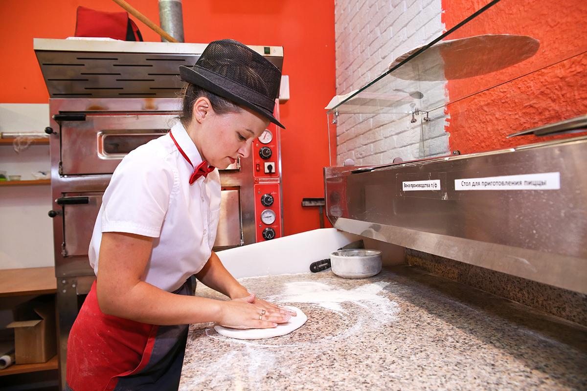 Повар-пиццер Ольга раскатывает тесто для пиццы.