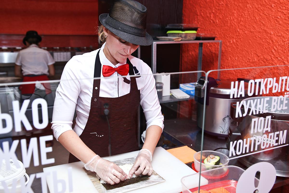 Повар-сушист Анастасия готовит роллы Филадельфия.