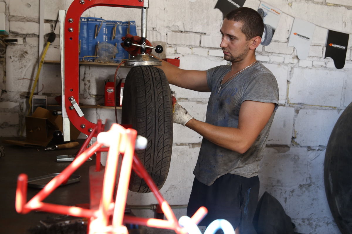 Максим Волчок выполняет демонтаж покрышки колеса легкового автомобиля.  Фото: Евгений ТИХАНОВИЧ